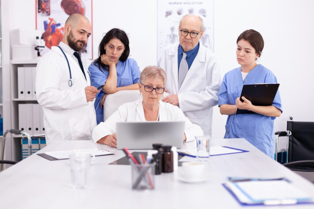 Team of doctors looking at laptop